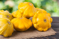 Yellow squash on a wooden table with napkin of burlap and blurred green background Stock Photo