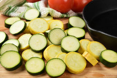 Yellow squash and zucchini. Sliced squash and zucchini by a cast iron skillet Royalty Free Stock Photos