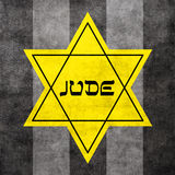 Yellow Star of David. Hexagram with text Jude on fabric striped background - typical star that Jews were forced to buy and sew on their clothes during World Royalty Free Stock Photos