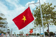 Vietnam flag flies in the wind on a city street