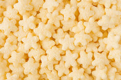 Yellow stars corn flakes closeup background, cereals texture. Stock Photos