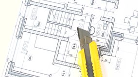 Yellow stationery knife on building plan, rotation stock footage