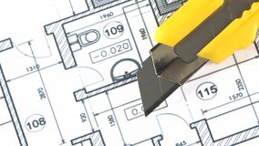 Yellow stationery knife on building plan, rotation stock video footage