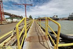 Yellow steel catwalk be access road for working in dock. Yellow steel catwalk be access road for working to shipyard crane in dock Royalty Free Stock Image