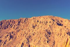 Yellow steep cliffs against the blue sky on the coast of the Arabian Sea royalty free stock image