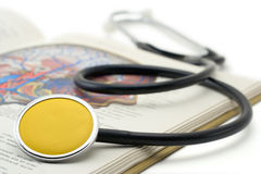 Yellow stethoscope on a book Royalty Free Stock Image