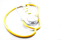 Yellow stethoscope with pills. Stethoscope with pills with isolated white royalty free stock photography