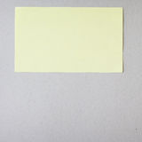 Yellow stick note on gray background Royalty Free Stock Photos