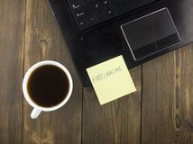 Yellow sticker with the inscription freelance on the laptop, a cup of coffee laptop royalty free stock photography