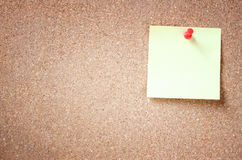 Yellow sticker pinned on a cork board Royalty Free Stock Image