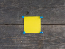 Yellow sticker and pins on  blue wooden wall Royalty Free Stock Photography