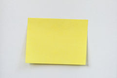 Yellow sticky note. Closeup of a small blank yellow sticky note stuck on a white wall royalty free stock images