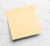 Yellow sticky note. A yellow sticky note on a gray background stock photography