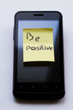 Yellow sticky note with  Be Positive. Photo serie about motivational stickers on mobile phone Royalty Free Stock Image