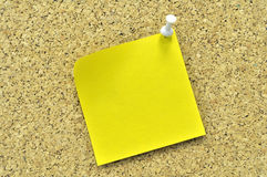 Yellow sticky note on a cork board. Royalty Free Stock Photo