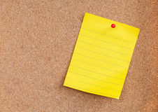 Yellow sticky note on cork board Stock Images