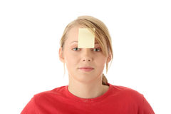 Yellow sticky note on forehead. Young woman in red tshirt with yellow sticky note on forehead. Isolated Stock Photo