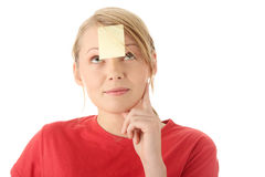 Yellow sticky note on forehead. Young woman in red tshirt with yellow sticky note on forehead. Isolated Stock Photography