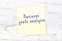 Yellow sticky note with handwritten text business goals analysis vector illustration