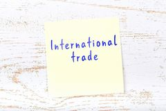 Yellow sticky note with handwritten text international trade stock illustration