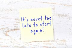 Yellow sticky note with handwritten text its nevet too late to start again stock illustration