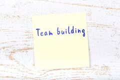Yellow sticky note with handwritten text team building stock illustration