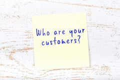 Yellow sticky note with handwritten text who are your customers royalty free illustration