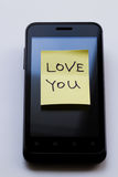 Yellow sticky note with  Love You. Photo serie about motivational stickers on mobile phone Royalty Free Stock Image