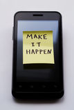 Yellow sticky note with  Make it happen. Photo serie about motivational stickers on mobile phone Royalty Free Stock Photos