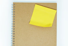 Yellow sticky note on notebook  background. Yellow sticky note on notebook background wallpaper Stock Image