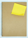 Yellow sticky note on notebook  background. Yellow sticky note on notebook background wallpaper Royalty Free Stock Image