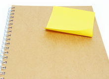 Yellow sticky note on notebook  background. Yellow sticky note on notebook background wallpaper Royalty Free Stock Photography