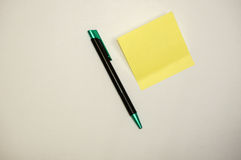 Yellow sticky note with pen Royalty Free Stock Photography
