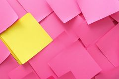 Yellow sticky note among pink ones. Difference and uniqueness concept stock photo