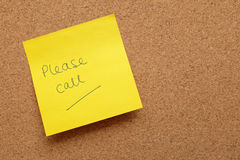 Yellow sticky note - Please Call - on cork board Stock Image