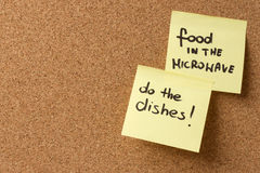 Yellow sticky note/ post it food in the microwave, do the dishes Stock Images