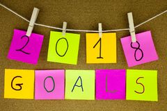 A yellow sticky note post it writing, caption, inscription for goals for 2018 year in black ext on a sticky note pinned to a cork Royalty Free Stock Photos