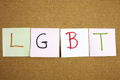 A yellow sticky note post it writing, caption, inscription LGTB Lesbian, gay, bisexual and transgender acronym in black ext on a s. Ticky note pinned to a cork Royalty Free Stock Images