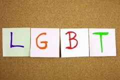 A yellow sticky note post it writing, caption, inscription LGTB Lesbian, gay, bisexual and transgender acronym in black ext on a s. Ticky note pinned to a cork Stock Photos