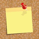 Yellow sticky note with a red push-pin against the background of cork board. Royalty Free Stock Photography