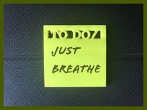 Just Breathe sticky note. Yellow sticky note reminder with just breathe text. Mental health concept Royalty Free Stock Image