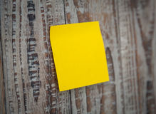 Yellow sticky note. On wooden board Stock Images