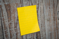 Yellow sticky note. On wooden board Stock Image