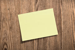 Yellow sticky note on wooden board. Royalty Free Stock Photos