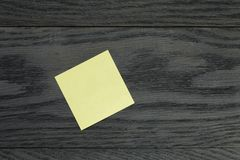 Yellow sticky note on wooden table Royalty Free Stock Image
