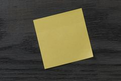 Yellow sticky note on wooden table Royalty Free Stock Images