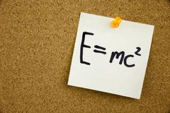 A yellow sticky note writing, caption, inscription EQUATION E EQUAL MC2 in black ext on a sticky note pinned to a cork. EQUATION E EQUAL MC2 in black ext on a stock images