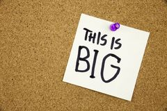 A yellow sticky note writing, caption, inscription Note paper with a text THIS IS BIG and black push pin on cork board. Note paper with a text THIS IS BIG and Stock Photos