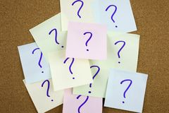 A yellow sticky note writing, caption, inscription Pile of colorful paper notes with question marks. Closeup. royalty free stock photos