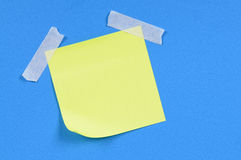 Yellow post-it style sticky note taped to blue background, copy space Royalty Free Stock Image